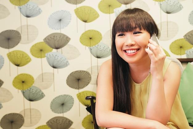 スマートフォンで話しているスマートカジュアルな若いアジアの女性をバーします。携帯電話で話す幸せな女性の大人。