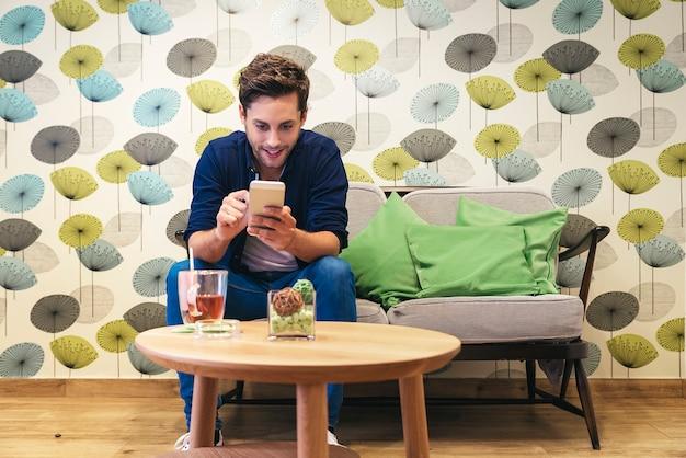 スマートフォンでメッセージを書くスマートカジュアルな若者をバーします。携帯電話でメッセージを書く幸せな男性の大人。