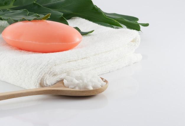 Кусковое мыло на чистых белых полотенцах, зеленые листья и солевой скраб на белых сценах для гигиены.