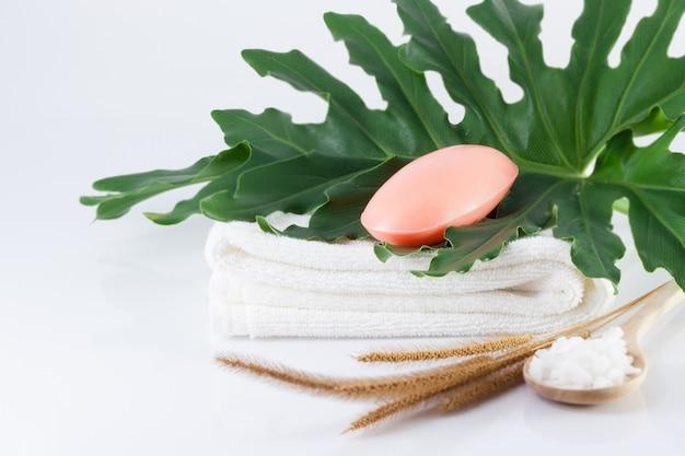 Кусковое мыло на чистых белых полотенцах, зеленые листья и соль для чистки на белых сценах для гигиены.