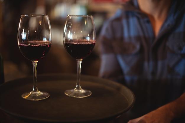 Барный тендер держит поднос с бокалами красного вина