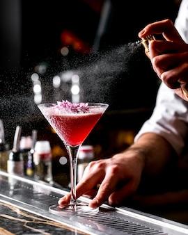 Bar tender sprays on cocktail glass garnished with flower
