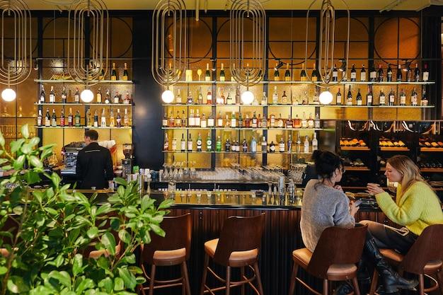 Бар с людьми и официантами с барной стойкой и большим количеством алкоголя интерьер в современном стиле