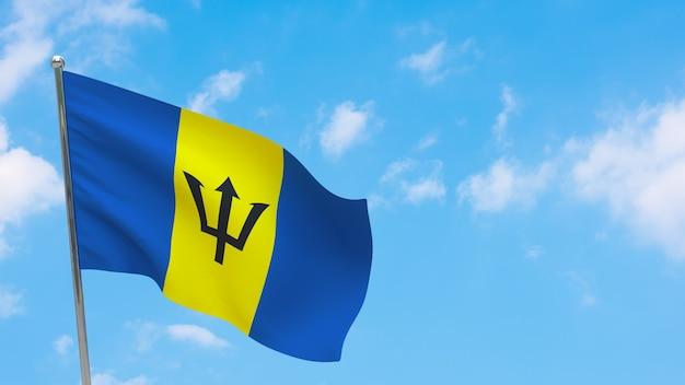 Флаг барбадоса на шесте. голубое небо. государственный флаг барбадоса