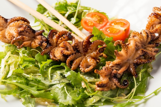 Barbecue baby octopus on white plate with herbs, tomatoes and sticks