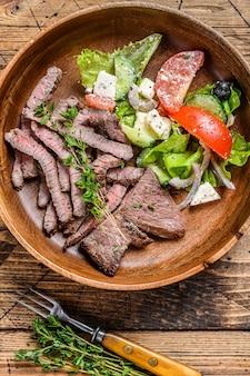 Стейк костреца отбивной мяса говядины барбекю на деревянной тарелке с овощным салатом.