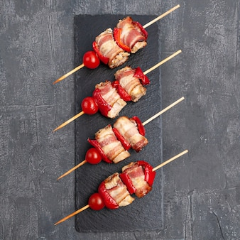 Barbecue chicken fillet with bacon, tomato and sweet pepper. on a dark slate board. view from above. gray concrete background.