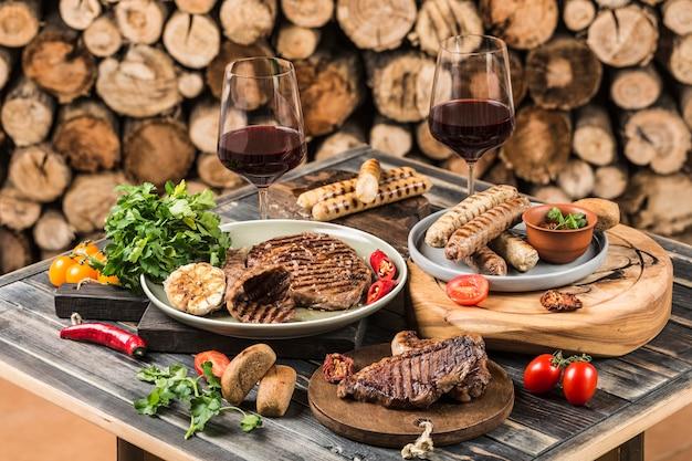 Шашлык из стейков из говядины, свинины, куриных колбасок, помидоров и перца чили, красного вина в бокалах на фоне мангала с дровами. вид сбоку с копией пространства.
