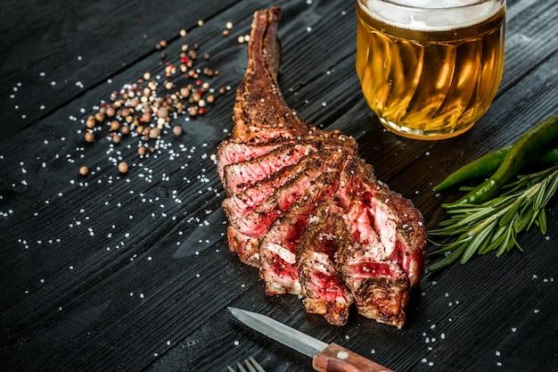 검은 나무에 양념 야채와 가벼운 맥주 한 잔을 곁들인 마른 숙성 쇠고기 갈비