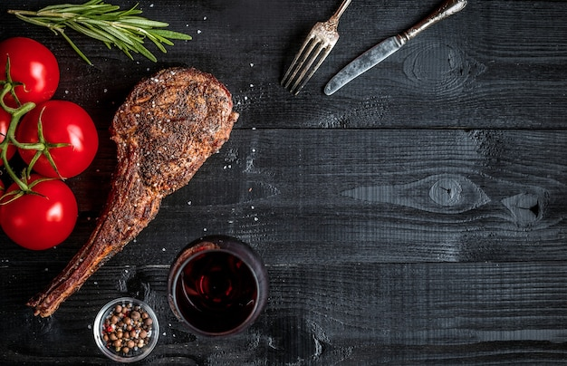 검은 나무 배경에 양념, 야채, 레드 와인 한 잔을 곁들인 마른 숙성된 쇠고기 갈비뼈. 평면도. 공간을 복사합니다. 정물. 플랫 레이