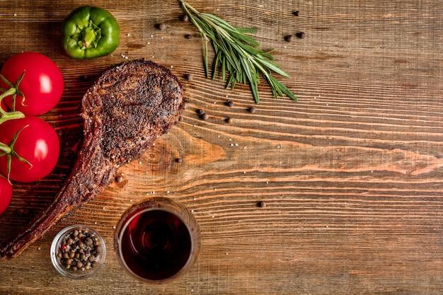 나무 배경에 클로즈업된 적포도주 한 잔과 야채를 곁들인 마른 숙성된 쇠고기 갈비. 평면도. 공간을 복사합니다. 정물. 플랫 레이
