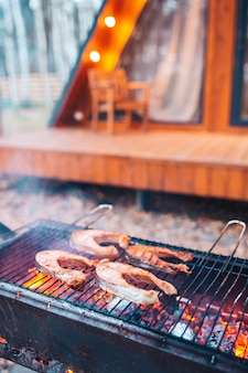 Barbecue fish steaks on the grill. fire and smoke roll over pieces of fish