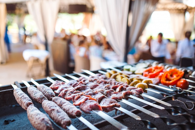 Barbecue from different types of meat in the restaurant on the background of the guests.