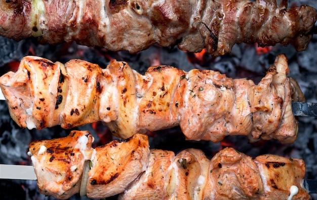 バーベキューグリル。牛肉と豚肉のシシュケバブを熱い石炭で揚げた串焼き。肉串のクローズアップ。バーベキュー串肉ケバブ。