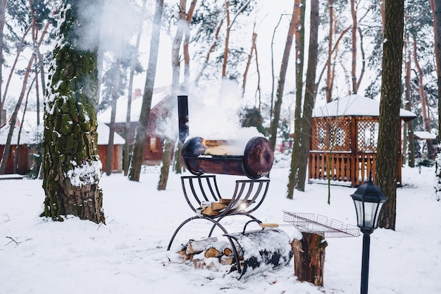 Barbecue grill in the snow-covered complex in smoke