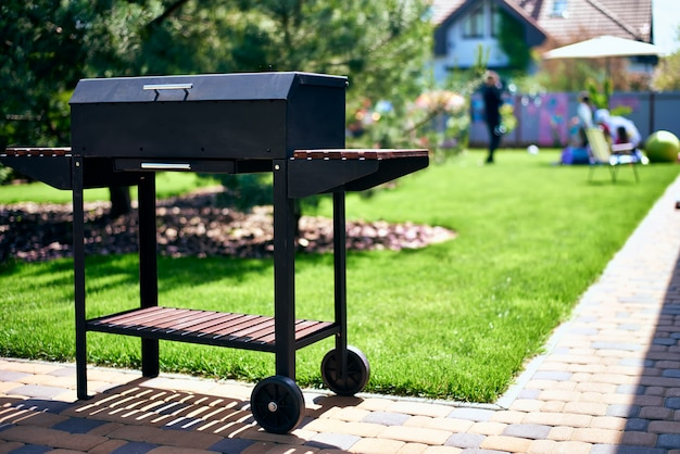 Barbecue grill on wheels with wooden stands in the garden