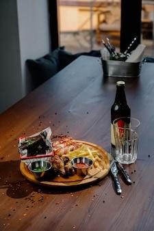 バーベキュー手羽先のグリルは、フライドポテト、木の板に醤油をクローズアップ。肉料理のコンセプトです。フライドチキンとフライドポテト。トップビュー