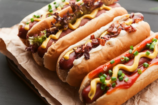 Barbecue grilled hot dogs with  yellow american mustard, on a dark wooden background