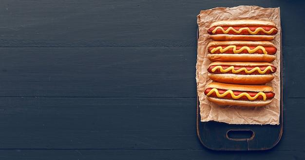 Жареные на гриле хот-доги с желтой американской горчицей, на темном деревянном фоне