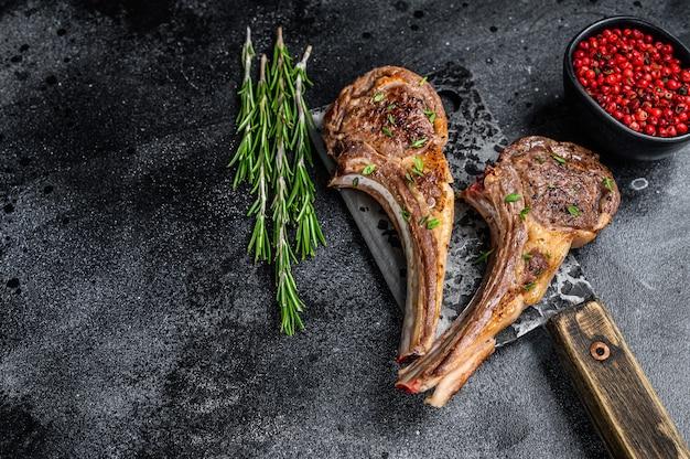 Бараньи отбивные, приготовленные на гриле, на нож для мяса. черный фон. вид сверху. скопируйте пространство.