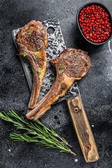 정육점 고기 칼에 바베큐 구운 양고기 볶음. 검은 배경. 평면도.
