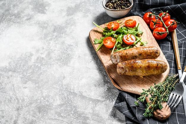 Шашлык из свинины на гриле колбаски с гарниром из томатного салата и рукколы