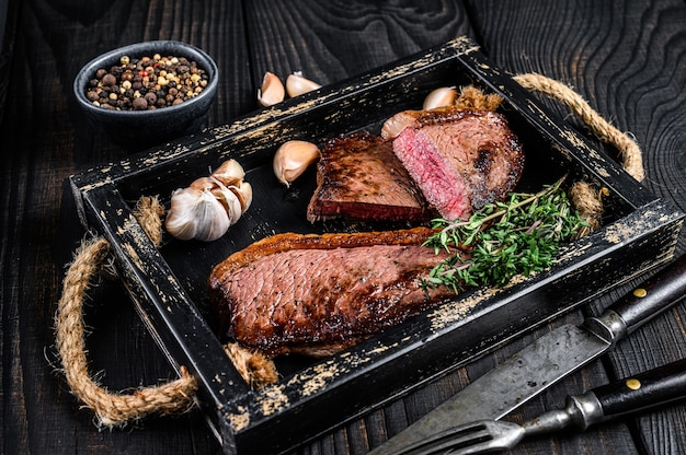 Barbecue grilled rump cap or brazilian picanha beef meat steak in a wooden tray. black wooden background. top view.