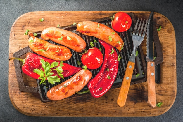 Barbecue. home hotdogs. grilled vegetables. sausages, tomatoes and peppers on a grilled baking sheet, cooked. with spices and herbs. with buns bread. on black stone table. copy space top view