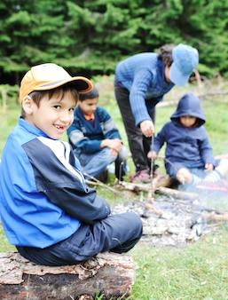 自然のバーベキュー、火のソーセージを準備する子供のグループ