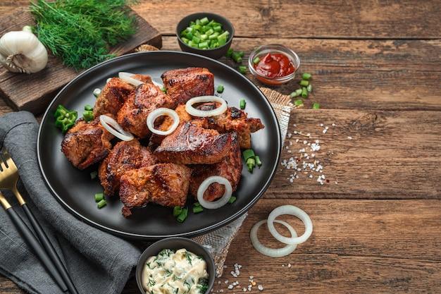 바베큐, 케밥, 튀긴 고기가 양파와 신선한 허브와 함께 접시에 깔려 있습니다. 측면 보기, 복사를 위한 공간입니다.