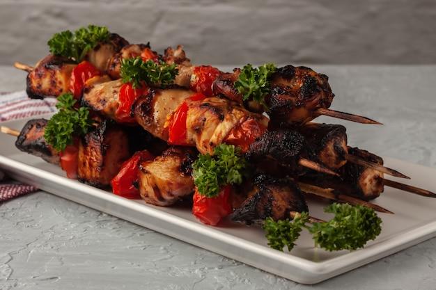 회색 배경에 야채와 꼬치에 닭 바베큐