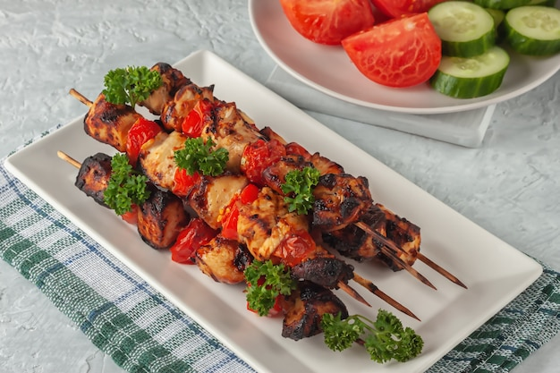 灰色の背景に野菜と串に刺した鶏肉のバーベキュー