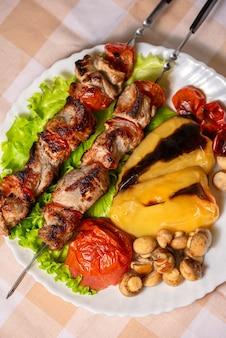 Шашлык на шпажках с салатом и запеченными овощами на белой тарелке обед на природе