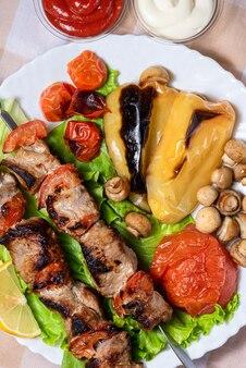 Шашлык на шпажках с салатом и запеченными овощами на белой тарелке