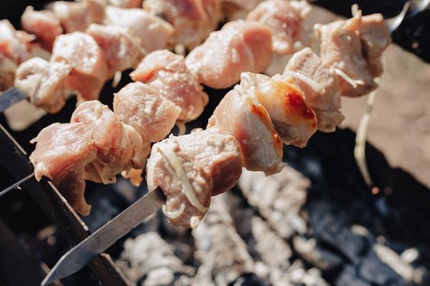 Барбекю на гриле в природе. готовить в огне. жареное мясо и еда.
