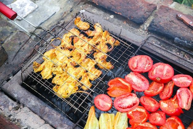모닥불에 바베큐. 달콤한 고추와 토마토입니다. 치킨 튀김.