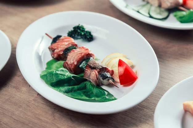 Шашлык на деревянных шпажках со свежими овощами.
