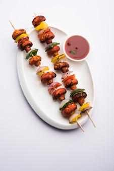 Шашлык или тандури mushroom tikka, подается в тарелке с зеленым чатни и кетчупом. выборочный фокус
