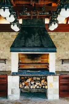 Печь для барбекю. большая печь-гриль в помещении, под ней дрова