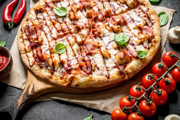 칠리 페퍼, 토마토, 시금치를 곁들인 바베큐 피자. 어두운 소박한