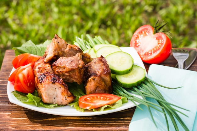 Barbecue on a plate with vegetables on a wooden table on the background of grass