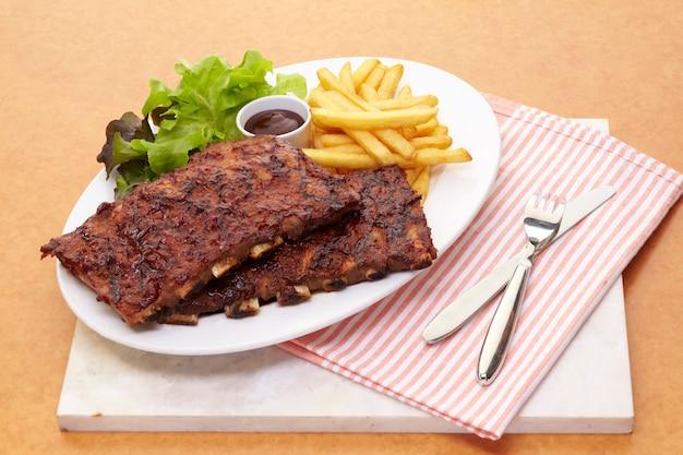 Свиные ребрышки барбекю подаются с жареной по-французски и салатом