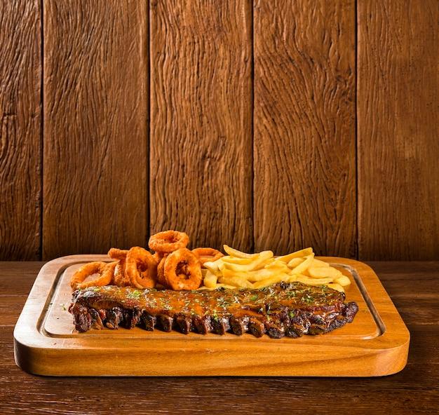 Свиные ребрышки барбекю с картофелем фри и луковыми кольцами.