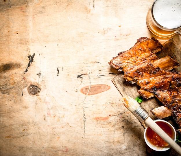 토마토 소스와 맥주 나무 배경에 바베큐 돼지 갈비