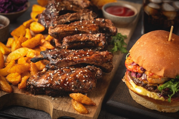 Barbecue pork ribs on a wooden board, potato wedges, burger and cola glass, sause. fast food. close-up.