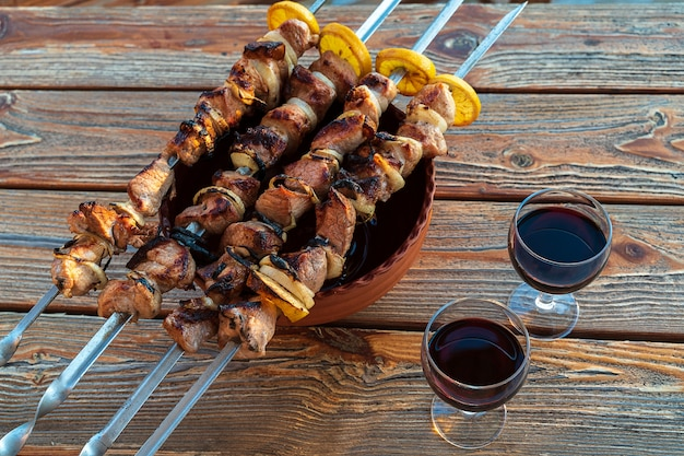 Barbecue prepared on grill and glasses of red wine, on wooden table.