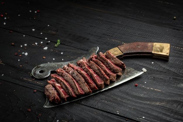ダークウッドの背景に古い肉切り包丁にバーベキューリブアイステーキランプステーキ乾燥熟成和牛。バナー、テキストのメニューレシピの場所、上面図。
