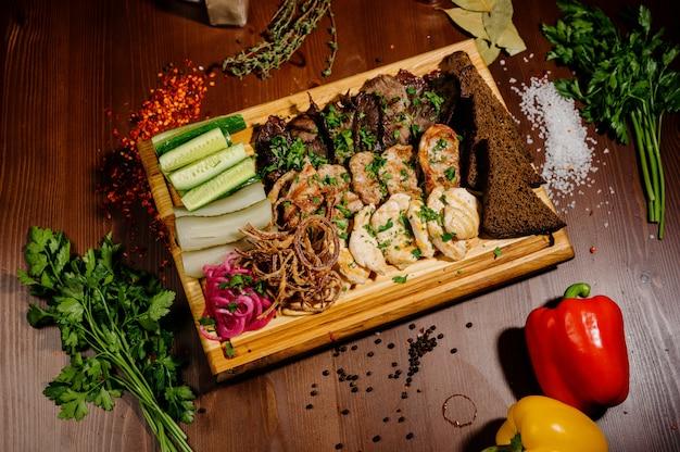 Ребра барбекю и картофель фри с соусом на деревянной тарелке. блюдо с большим количеством жареного мяса. вид сверху