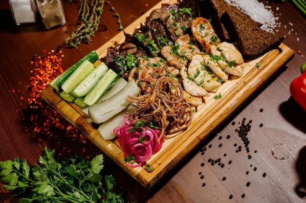Ребра барбекю и картофель фри с соусом на деревянной тарелке. блюдо с большим количеством жареного мяса.