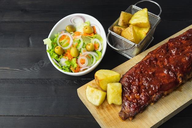 Ребрышки барбекю с картофелем и салатом на деревянной доске на темном фоне. скопируйте пространство.